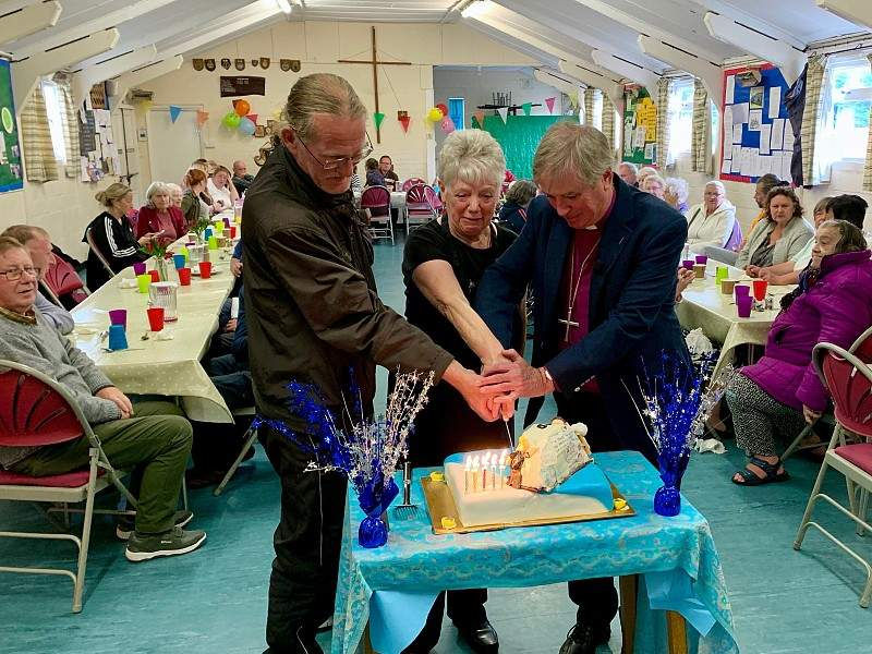 Bishop Jonathan, Paul and Maggie cutting the celebration cake
